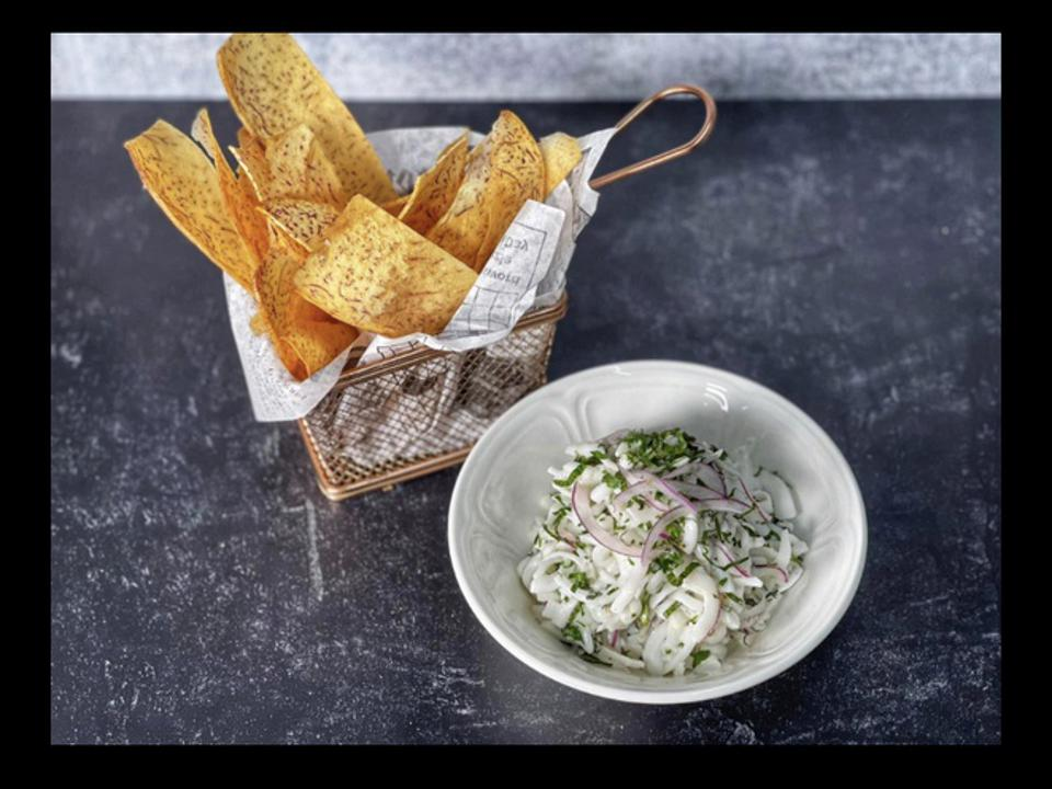 A basket filled with taro chips and a side of fresh coconut made like ceviche