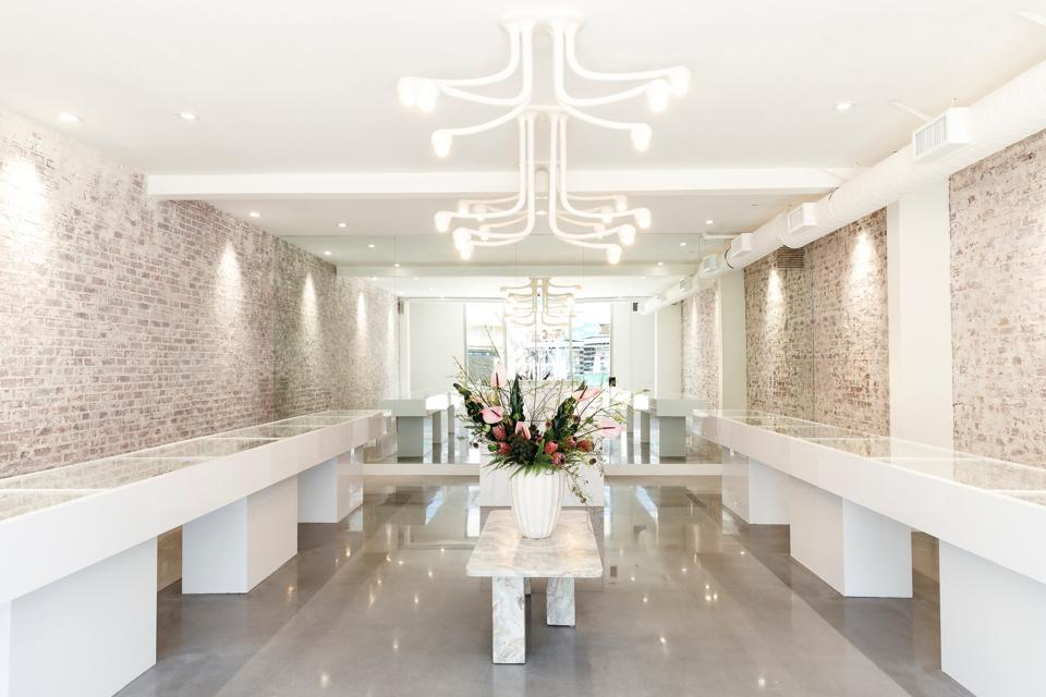 A jewelry store interior with whitewashed brick walls, concrete floor and white cabintetry