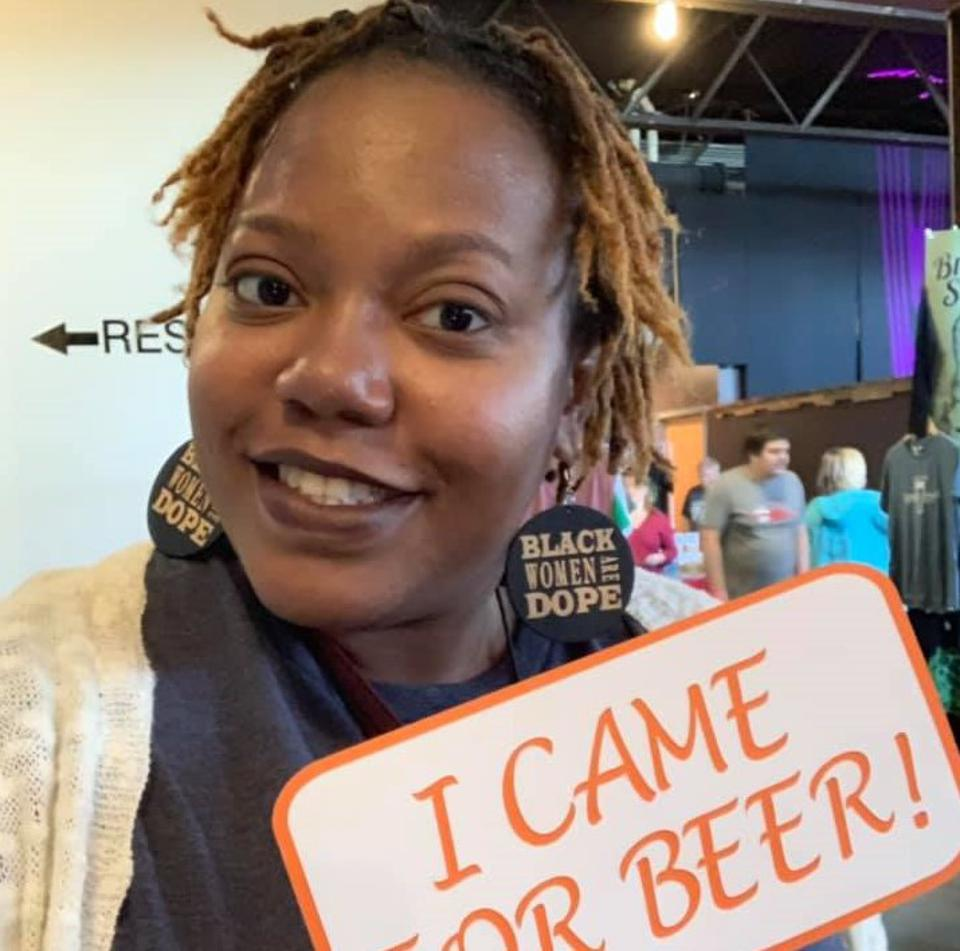 A Black woman smiling holding a sign that says, ″I came for beer!″