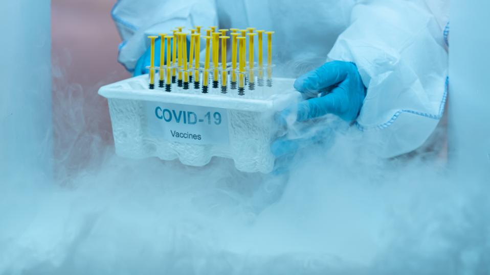 Medical staff distributing covid-19 vaccine tray inside the freezer. Healthcare and medical concept