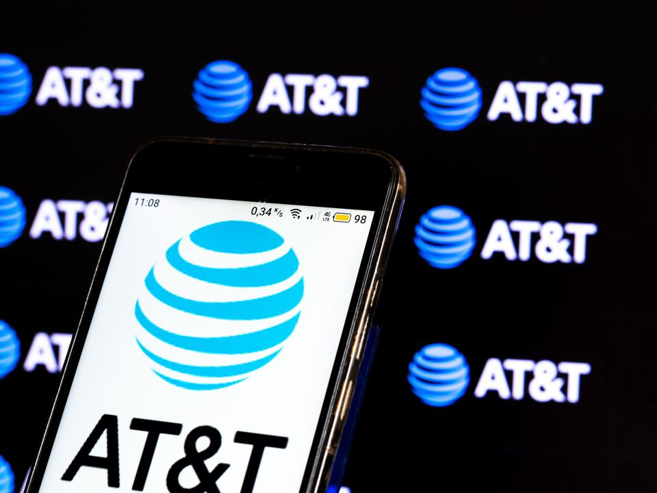 In this photo illustration a AT&T logo seen displayed on a...