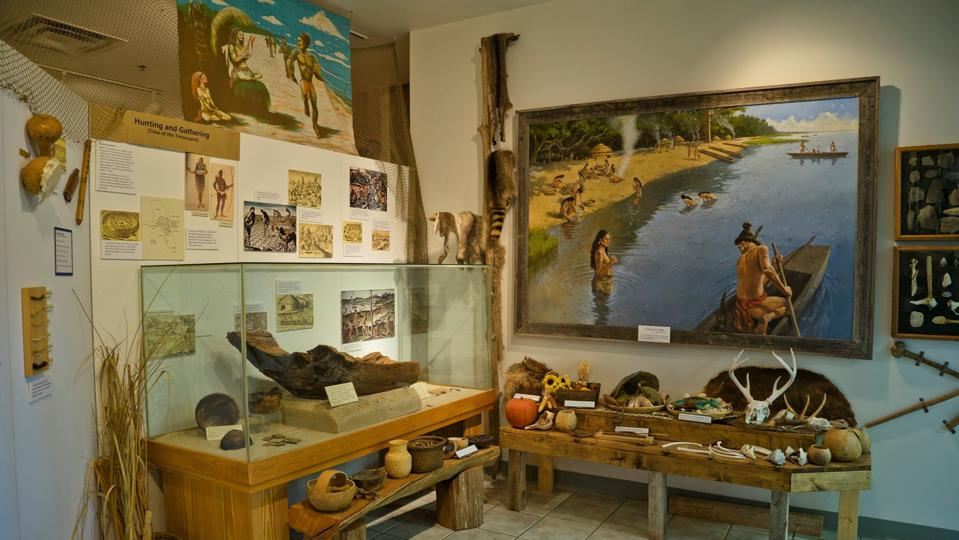 A history museum featuring a painting of the indigenous tribes of Georgia next to many artifacts