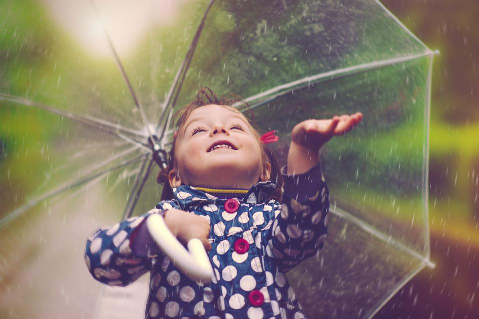 Happy baby girl in rain with clear umbrella
