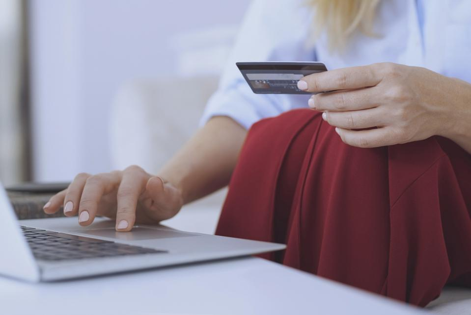 Blond woman sitting on couch, using laptop to make a payment with her credit card