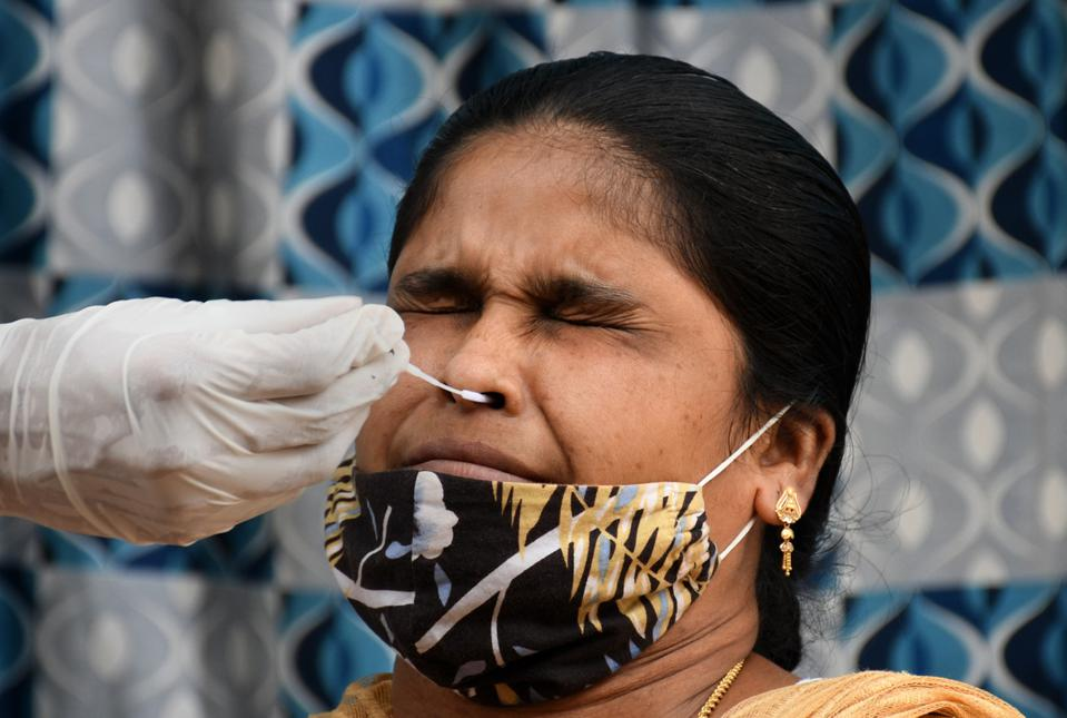 A healthcare worker collects a swab sample from a woman...