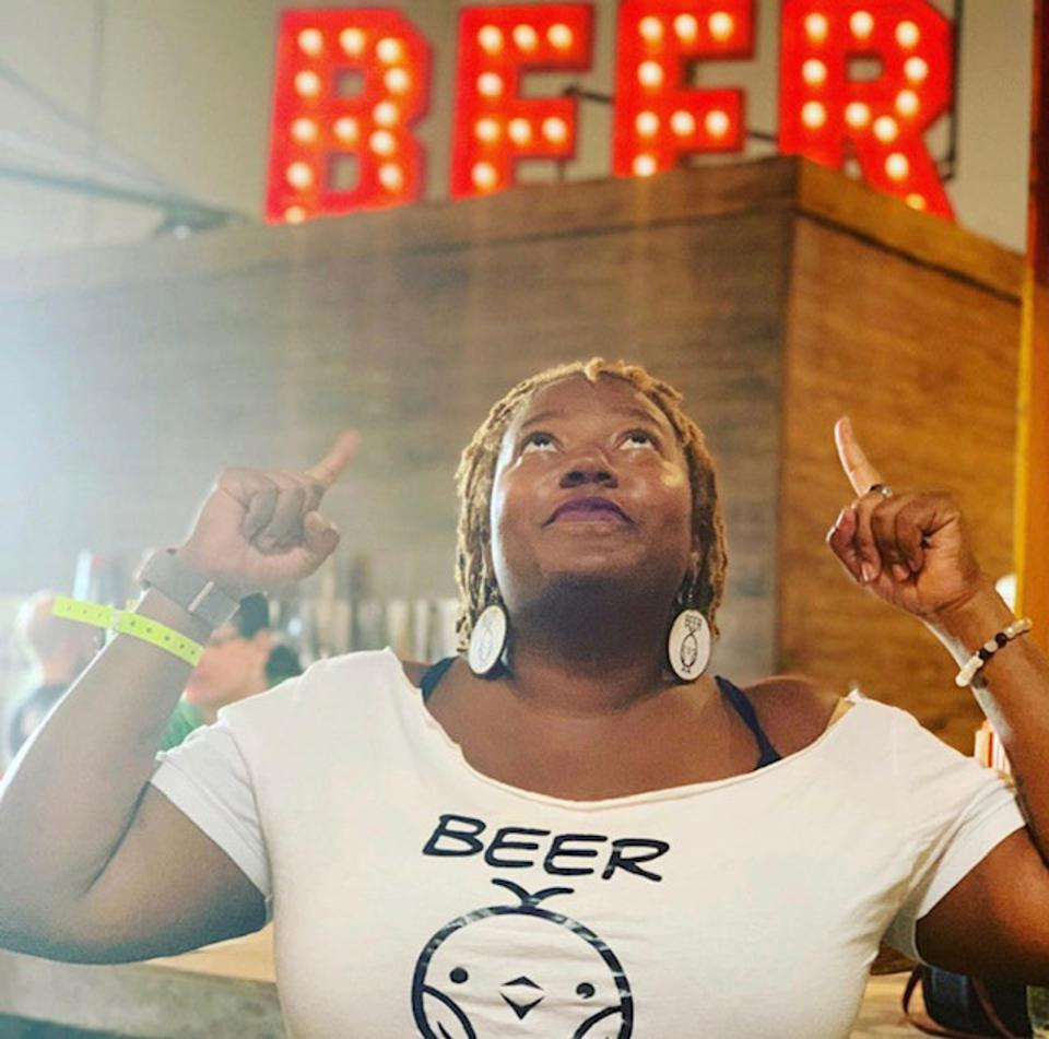 A Black woman wearing a beer t-shirt pointing up at a neon sign that says ″beer.″