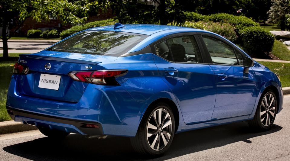 A bright-blue, 2021 Nissan Versa small sedan, parked in bright sunshine.