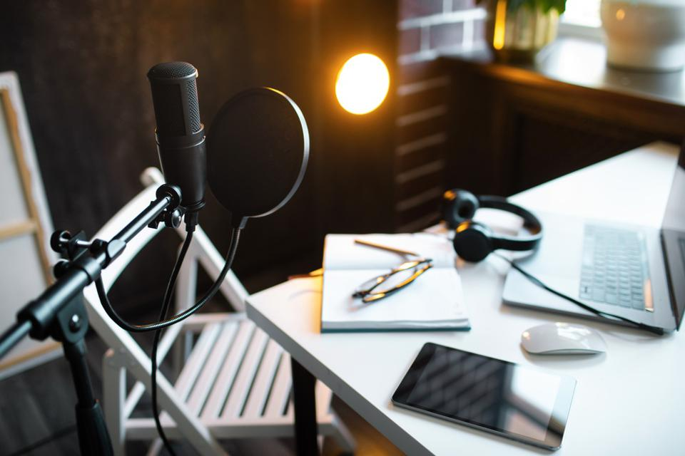 Podcast streaming at home. Audio studio with laptop, microphone with pop filter and headphones on white table against black wall with warm lights. Blogger concept.