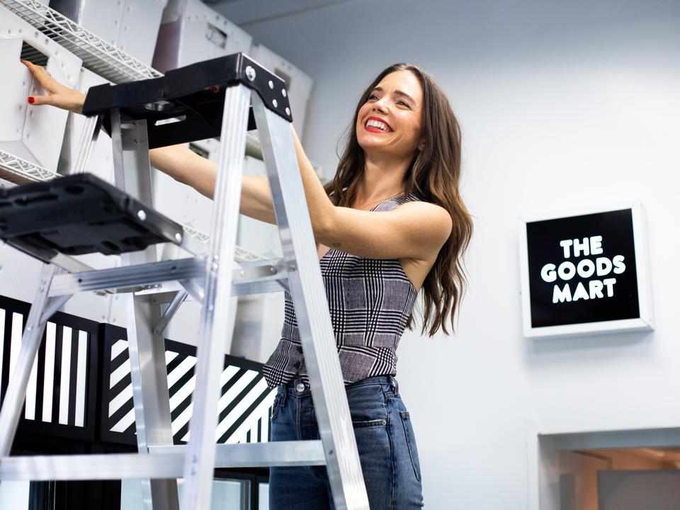 Krupa stands on a ladder stocking shelves with black and white bins.