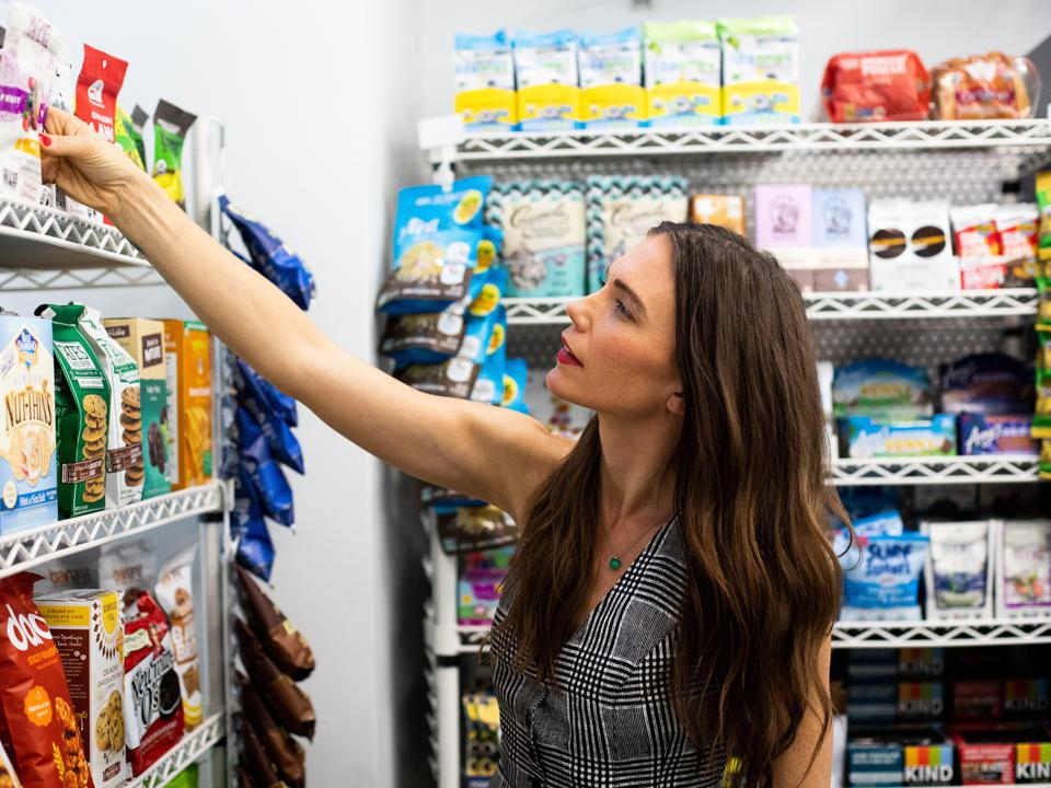 Krupa reaches for a snack on her store shelves stocked with products.