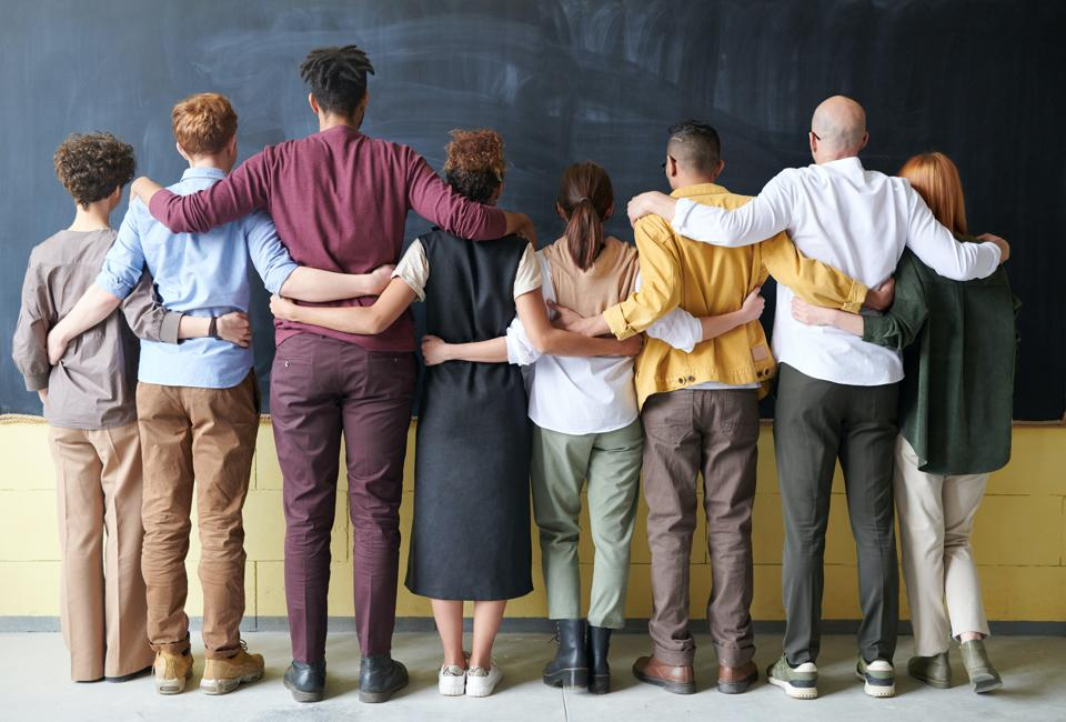 eight people standing with their backs to the camera with hands over each others' shoulders