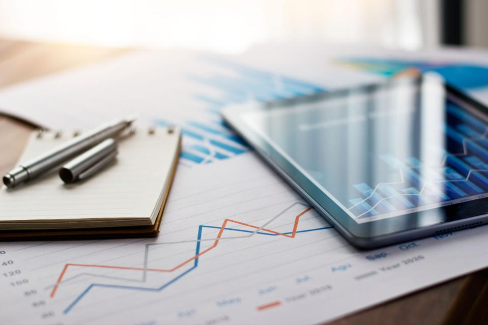 Business document report on paper and tablet with sales data and financial business growth graph on table background.
