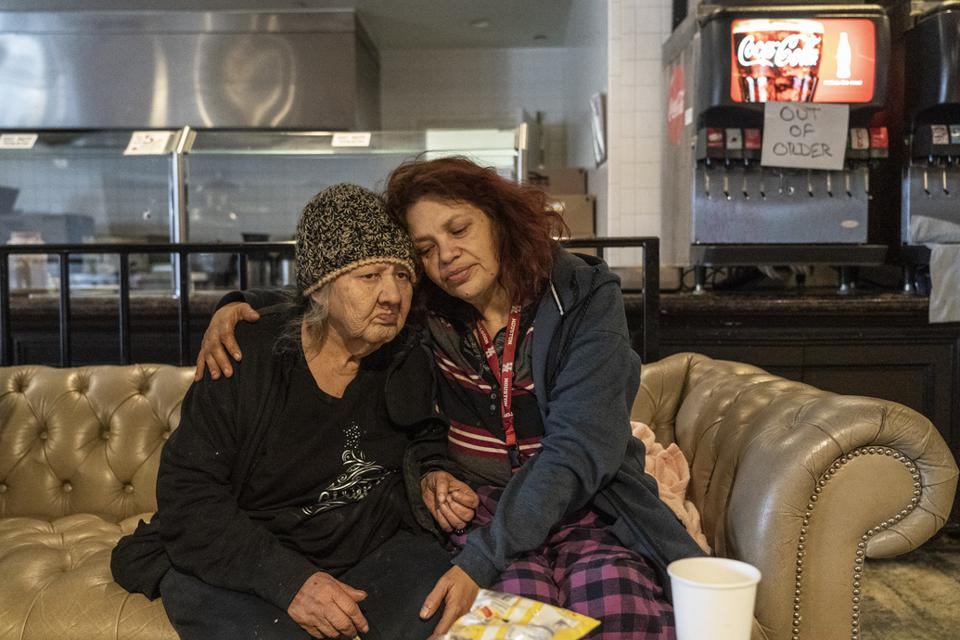 HOUSTON, TX - FEBRUARY 18:  Deloris Sanchez, 56, and Mallissa Lee, 52, sit on a couch while taking shelters at Gallery Furniture store which opened its door and transformed into a warming station after winter weather caused electricity blackouts on February 18, 2021 in Houston, Texas.  (Photo by Go Nakamura/Getty Images)