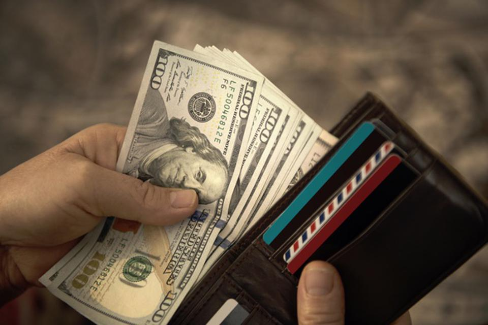 man pulling $100 bills out of wallet.