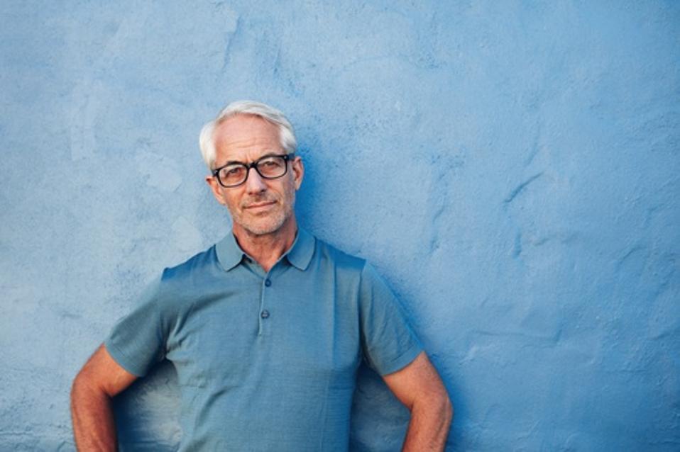 Mature man standing against a blue wall