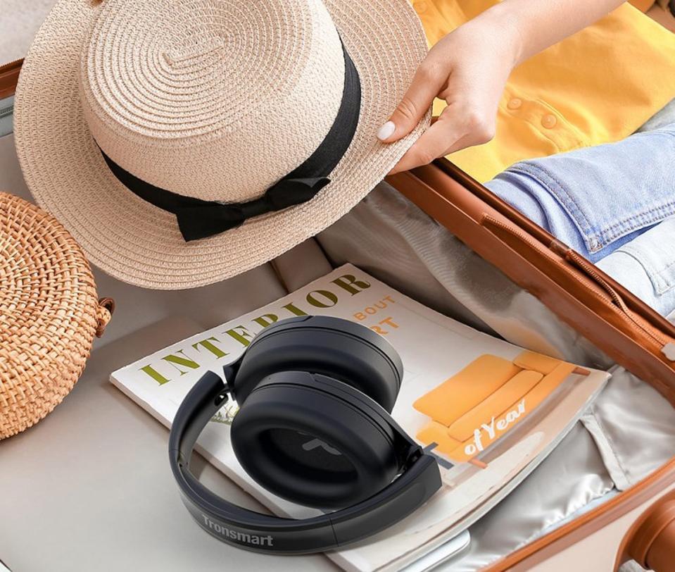 A pair of Tronsmart Apollo Q10 headphones  resting on a magazine