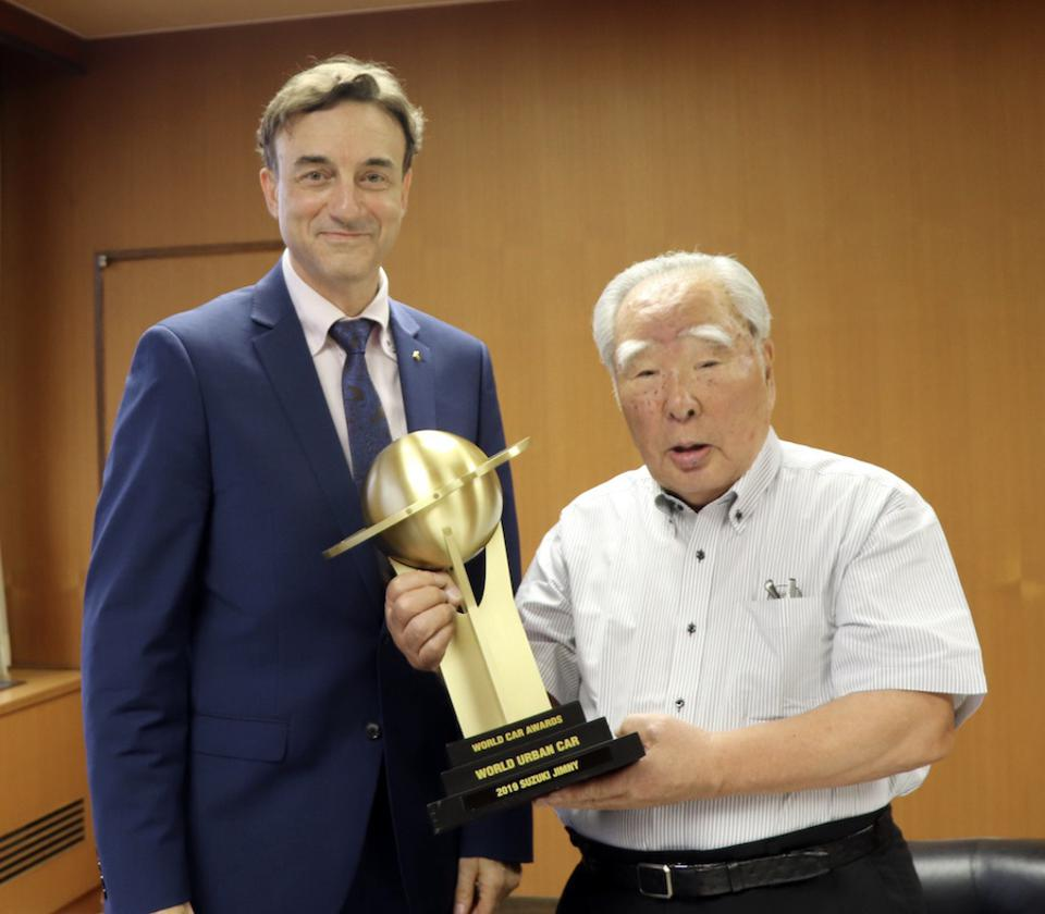 The writer presents the World Urban Car trophy to Chairman Suzuki at their Japan headquarters in 2019.