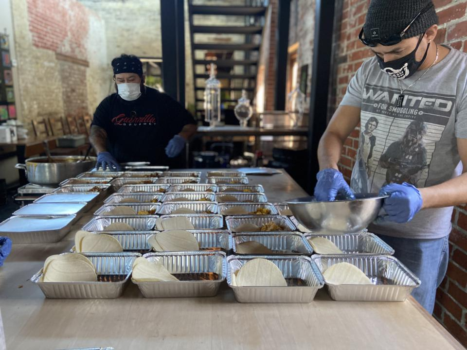 Two workers packaging takeout meals