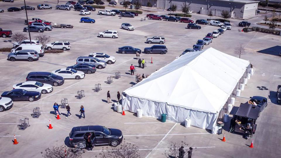 Large tent in parking lot and line of cars in wait for food.