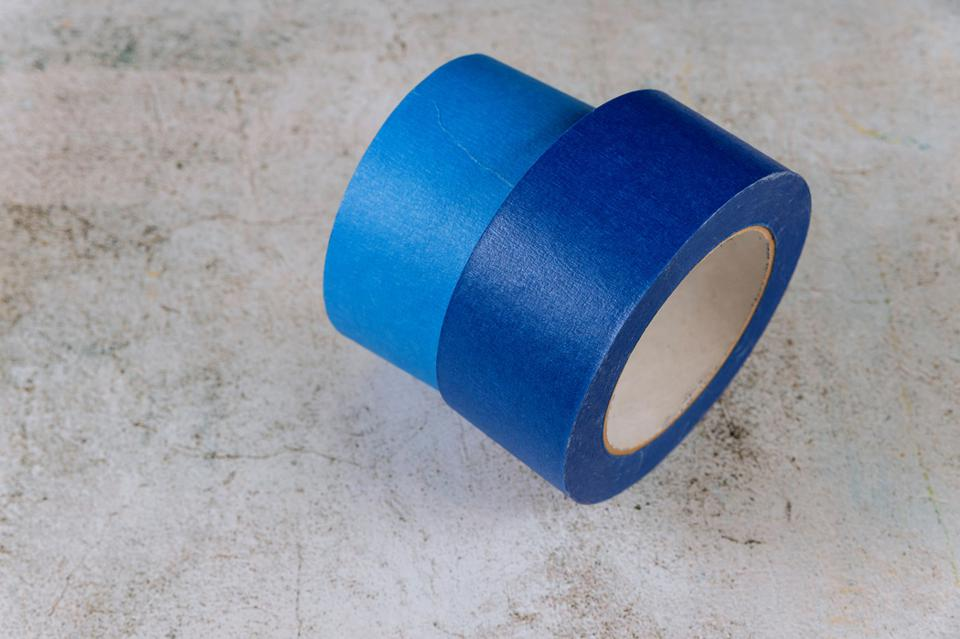 Blue painter tape for multi surfaces on white wall background.