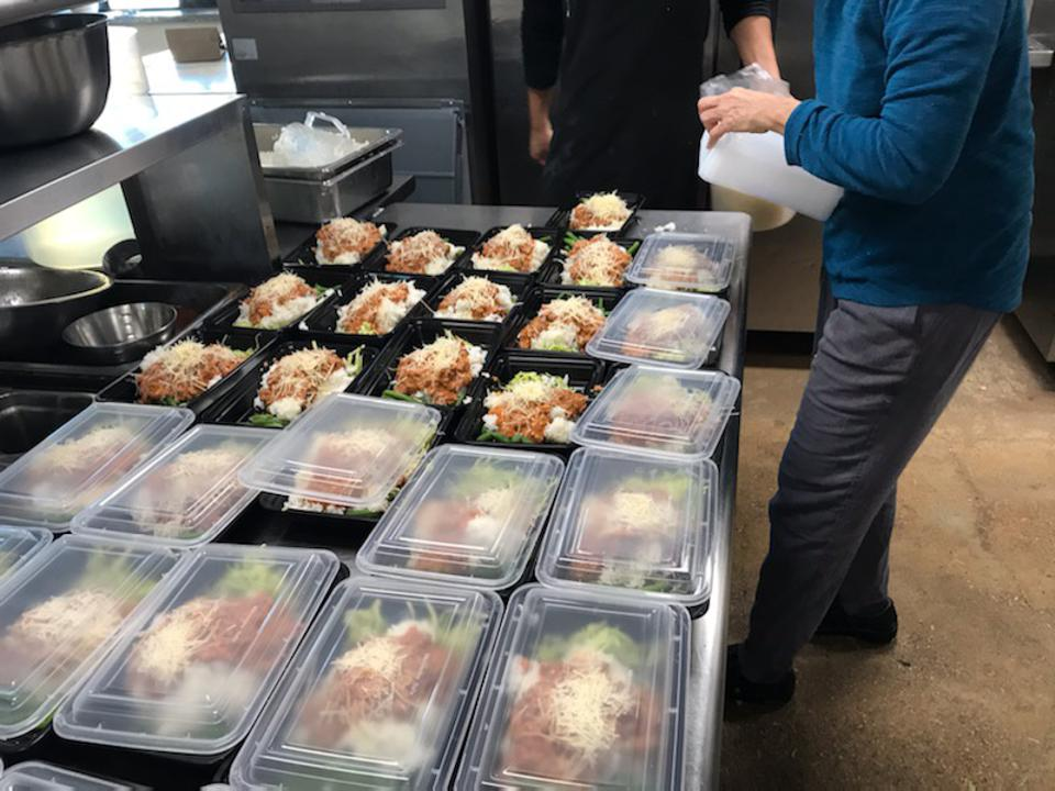 Kitchen worker packaging meals to go.