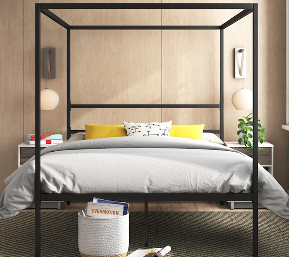 black bed frame in a wood-paneled bedroom