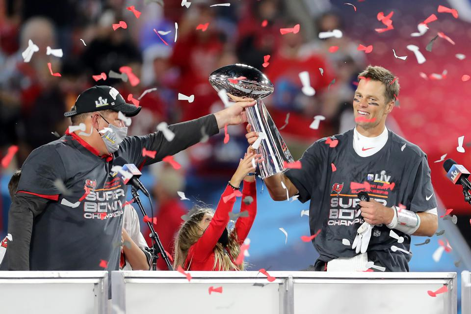 Super Bowl MVP Tom Brady of the Bucs accepts the Lombardi Trophy from Jason Licht