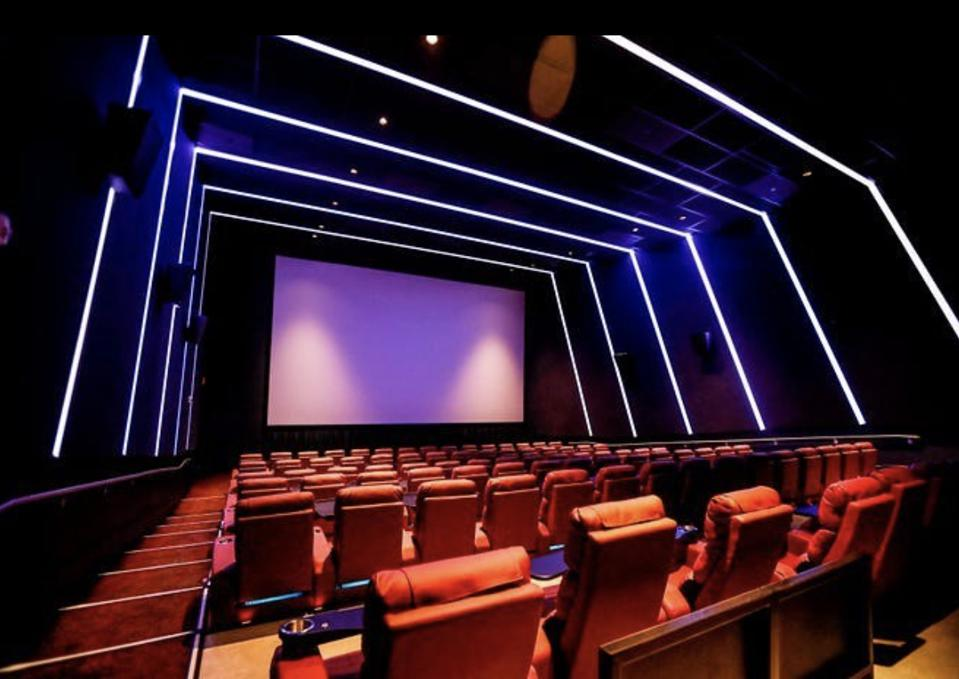 modern movie theater with recliners and neon lights