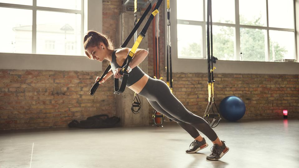 Working hard. Side view of young athletic woman with perfect body in sportswear doing push ups with trx fitness straps in the gym