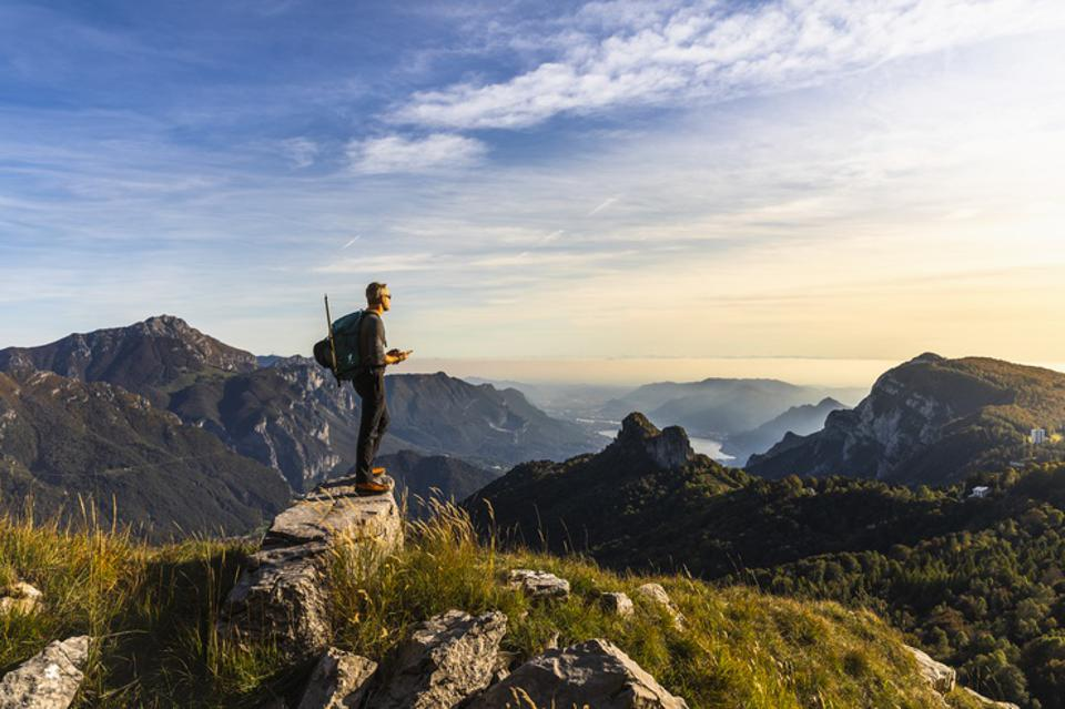 Hiker Alone Looking at View From Mountain Top