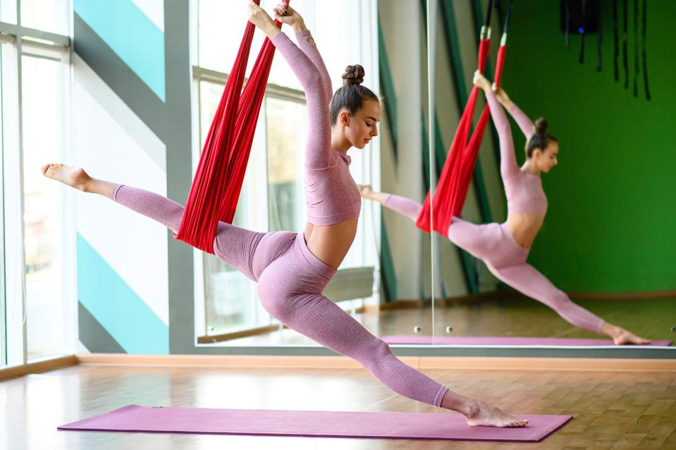 Slim athletic woman in hammock do aerial yoga and stretching exercises. Sport motivation and healthy lifestyle
