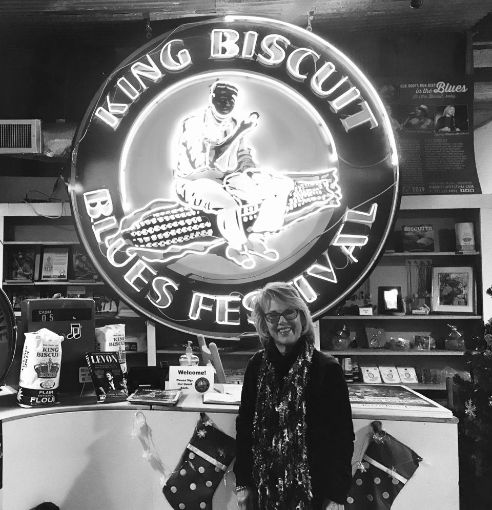 A black and white image of woman standing in front of a siign that says King Biscuit Blues Festival