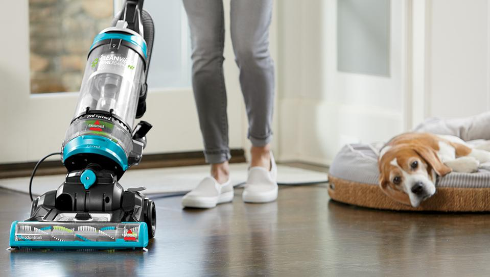 Woman cleaning the floor with the BISSELL Cleanview Swivel with a dog lying in bed