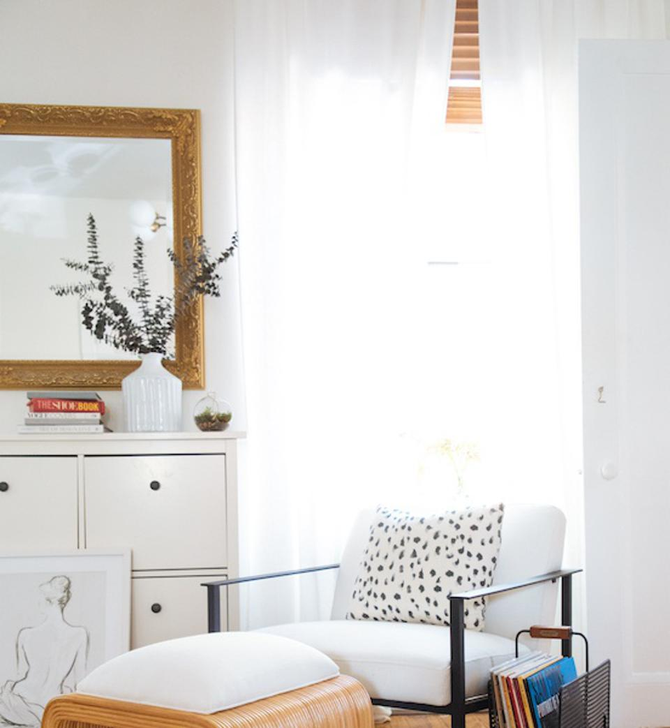 A corner with a white curtain, chair and Dalmatian style pillow