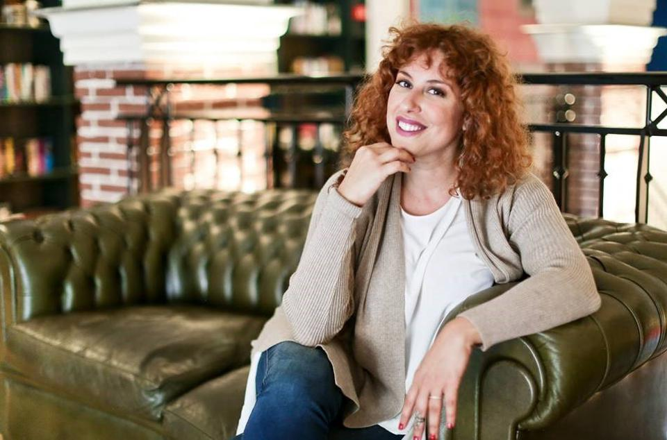 Cherine Kurdi sitting on a green sofa, and she has flaming red hair.