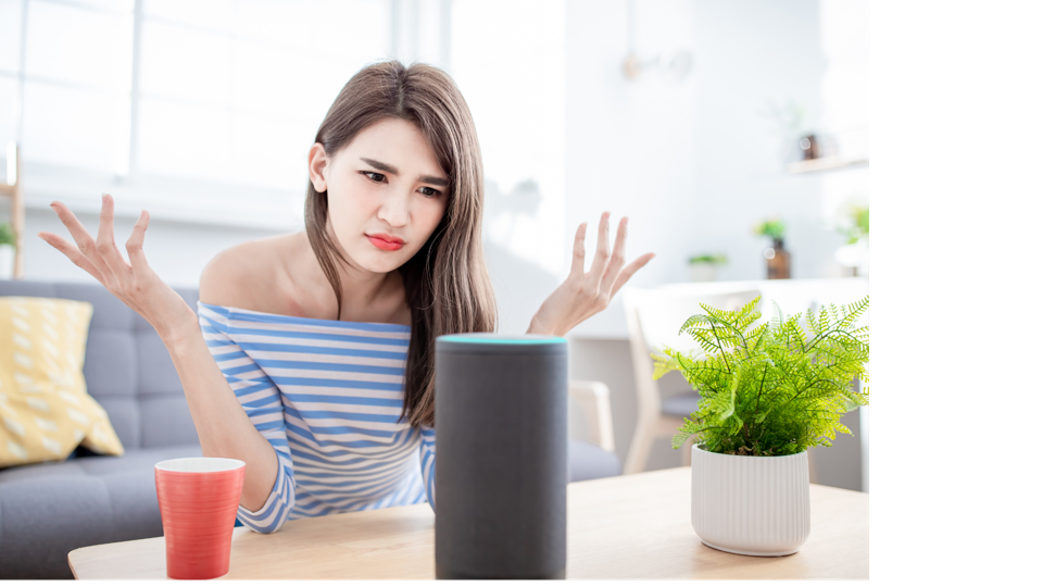 A woman is throwing up her hands because she does not understand what a digital assistant is telling her.