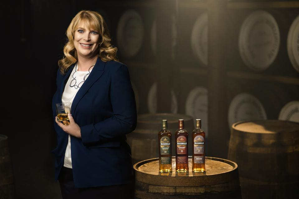 Helen Mulholland, master blender for Bushmills Irish whiskey (blonde woman with curly hair wearing a blur blazer, white blouse and necklace) holding a glass of Irish whiskey