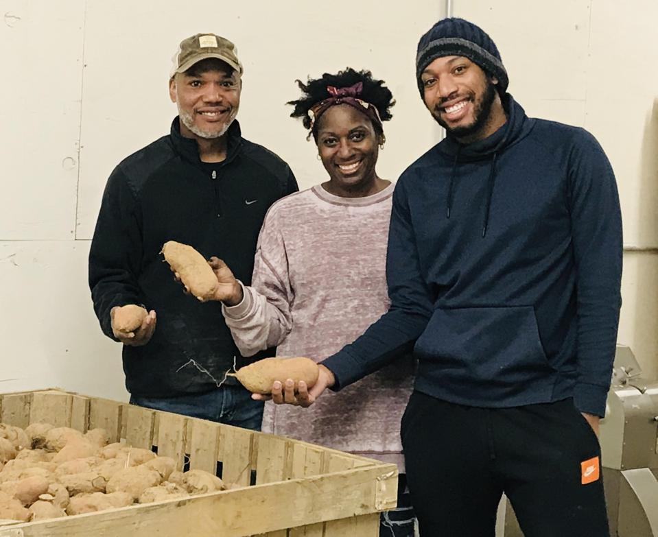 Two Black men and a Black woman stand holding sweet potatoes.
