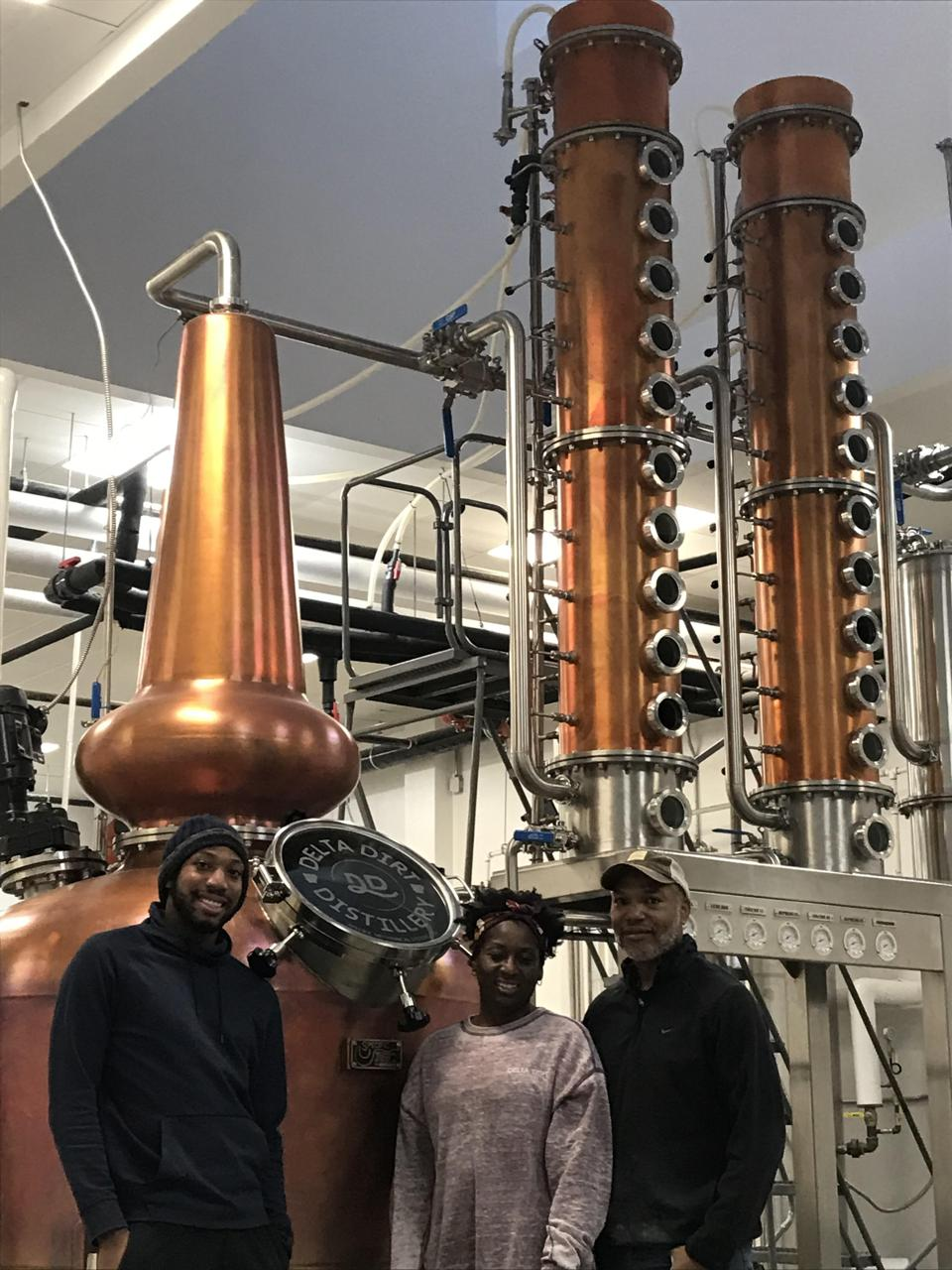 Three people standing in front of large columns of distilling equipment.