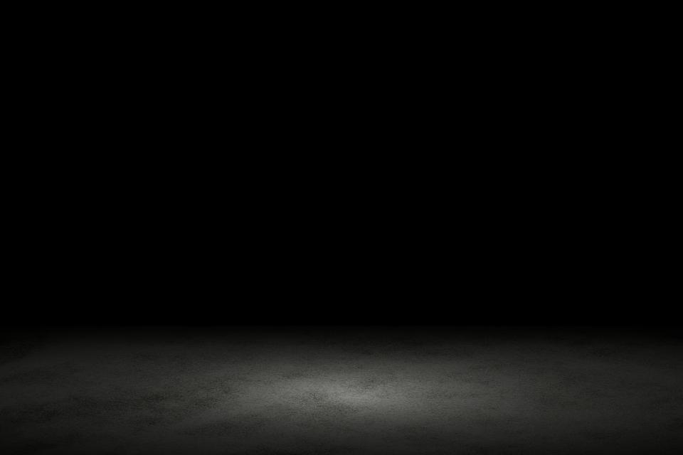La lumière brille sur le sol de marbre noir dans une pièce sombre avec un espace de copie, fond abstrait