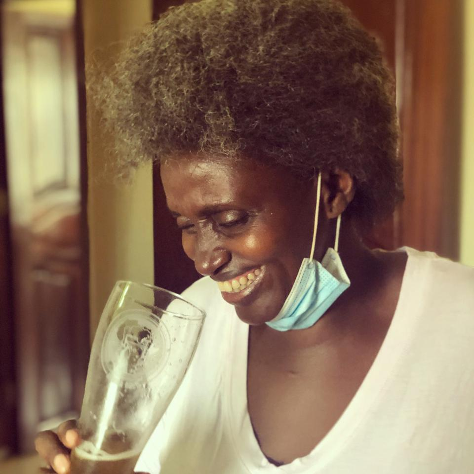 A Rwandan woman smiling holding a beer