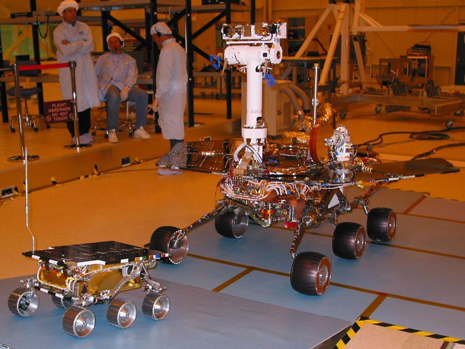 color photo of small Mars rover and large Mars rover with three humans in shower caps in the background