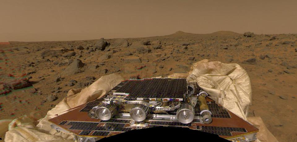 Color photo of a small Mars rover on a solar panel, with rocky brown terrain in the background.