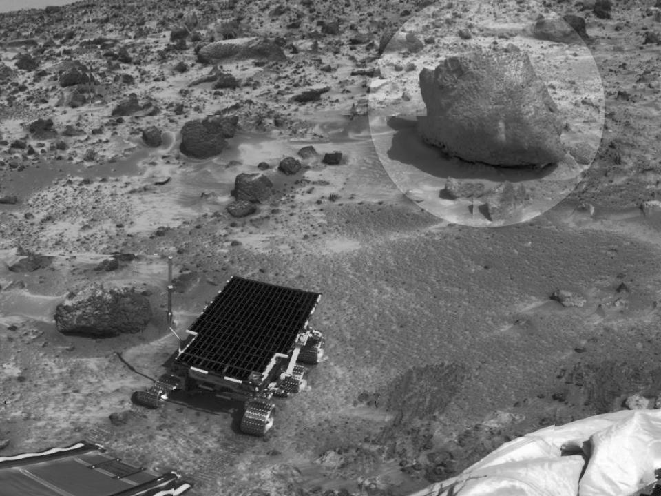 Black and white photo, from above, of Mars rover at the foot of a ramp, rolling towards a large rock.