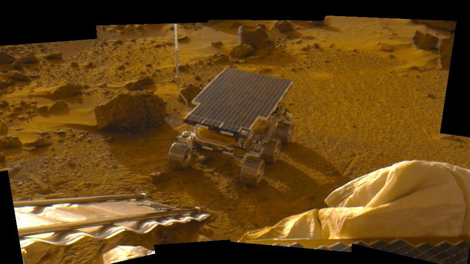 Color photo of a Mars rover at the foot of a ramp on rocky brown terrain.