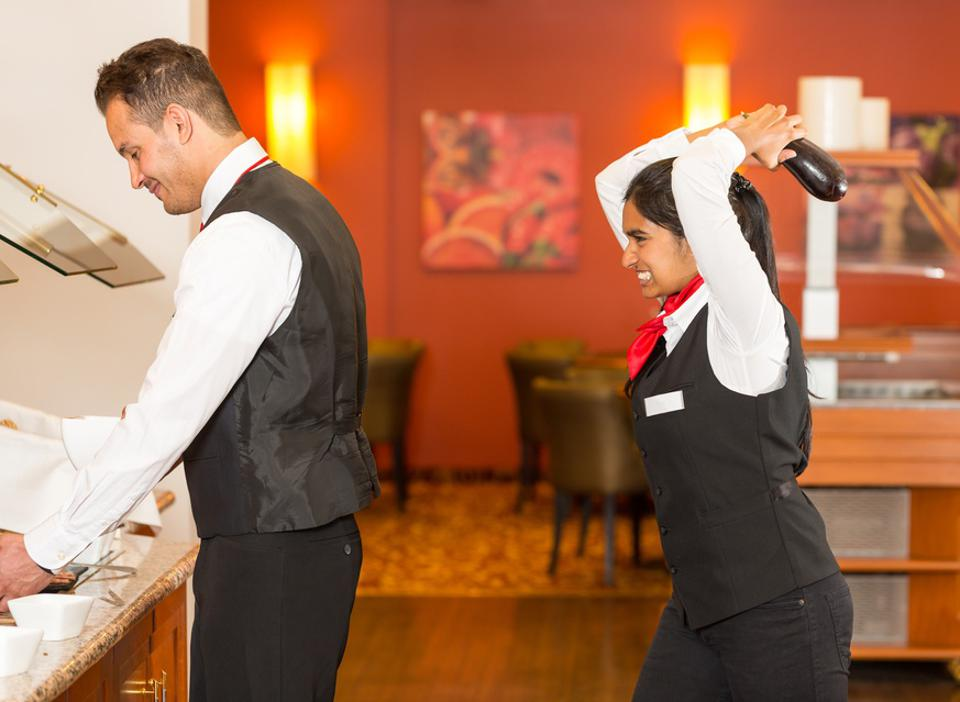 Frustrated waitress trying to hit colleague with cucumber