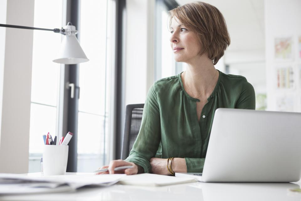 Businesswoman at office desk thinking