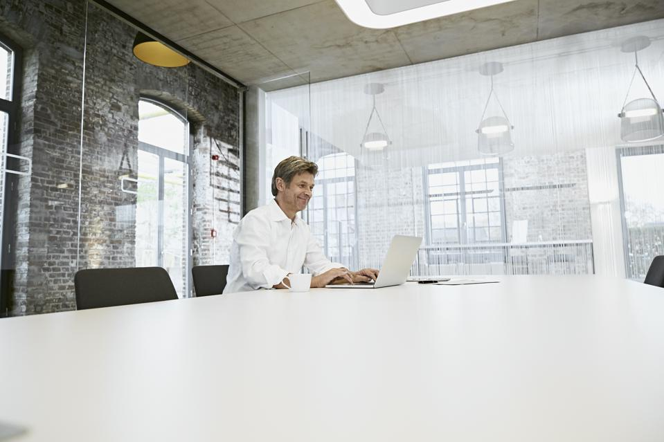 Mature businessman in bright modern conference room using laptop