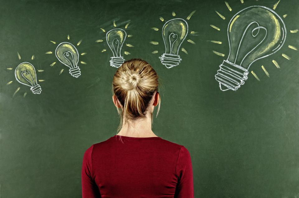Young Woman Looking at Light Bulbs Sketched on Blackboard