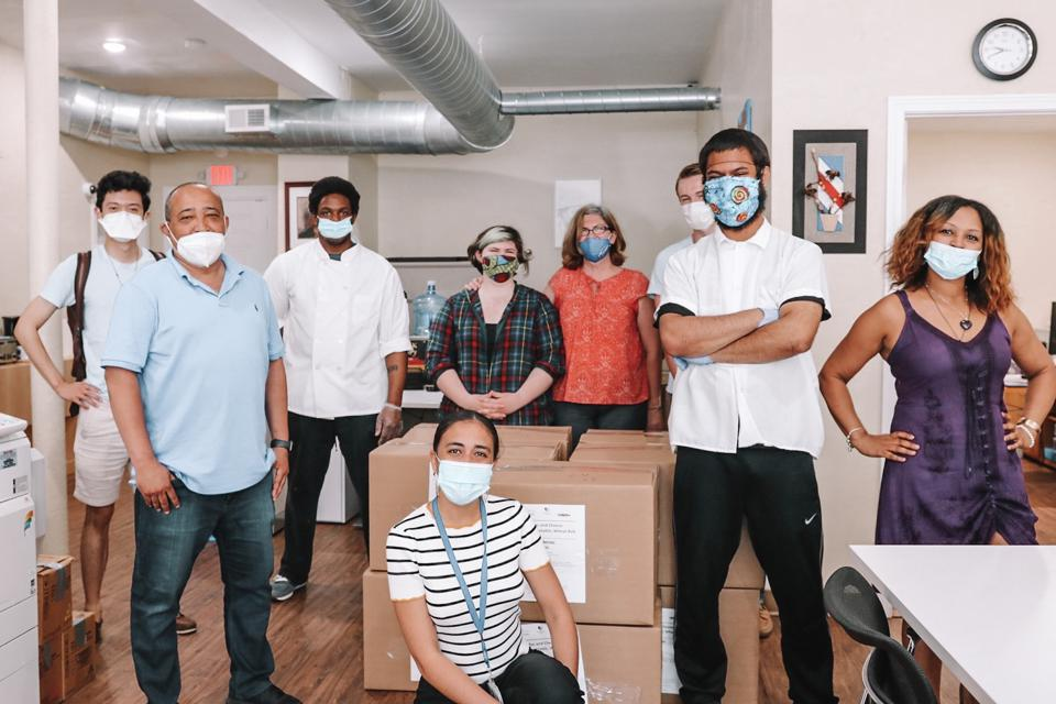 A team of employees gathered together wearing masks